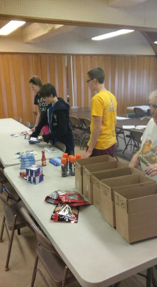 Youth prepare care packages for soldiers & college students.